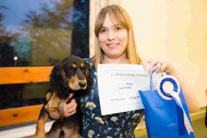 Cocker Spaniel puppy owner holding puppy with Puppy School certificate and rosette on graduation