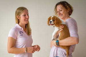Puppy School tutor talking to owner holding a Cavalier King Charles Spaniel puppy