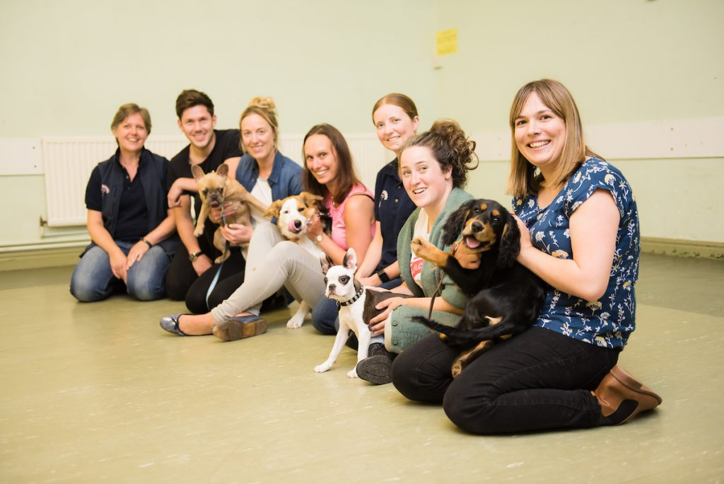 Puppy School tutor and owners kneeling holding puppies